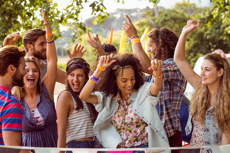 outdoor activities: Happy hipsters dancing to the music at a music festival Stock Photo