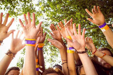 escapism: Happy hipsters with hands up at a music festival Stock Photo