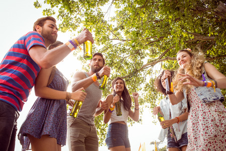 spring festival: Happy hipsters dancing to the music at a music festival Stock Photo