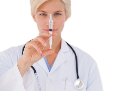 Doctor showing syringe to camera on white background photo