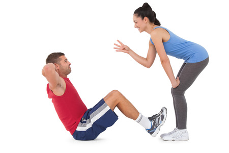 personal trainer woman: Trainer counting man doing sit ups on white background Stock Photo