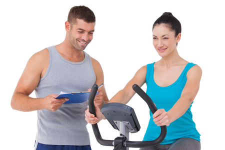 personal trainer: Trainer with client on exercise bike on white background Stock Photo