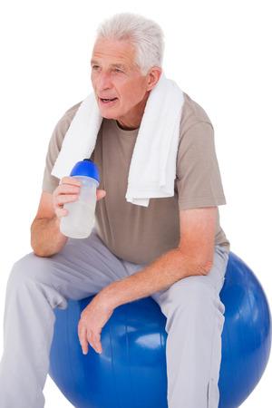 taking a break: Senior man taking a break from exercise on white background