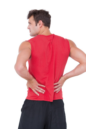 muscle pain: Fit man with injured back on white background