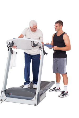 adult  body writing: Senior man on treadmill with trainer on white background Stock Photo