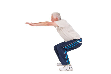 squat: Senior man doing a squat on white background