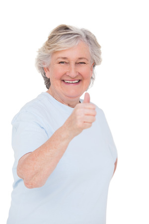 thumbs up gesture: Senior woman showing thumbs up on white background Stock Photo