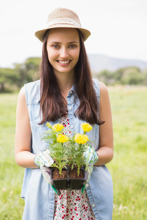 country living: Happy woman holding potted flowers on a sunny day