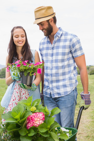 Happy young couple gardening together on a sunny day photo