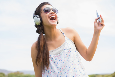 youngster  girl: Pretty brunette listening to music on a sunny day