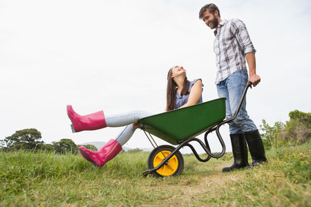 Man pushing his girlfriend in a wheelbarrow on a sunny day photo