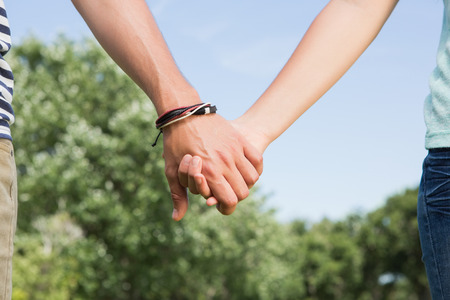 cogidos de la mano: Cute couple in the park holding hands on a sunny day Foto de archivo
