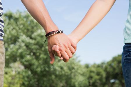 holding hands: Linda pareja en el parque de la mano en un d�a soleado