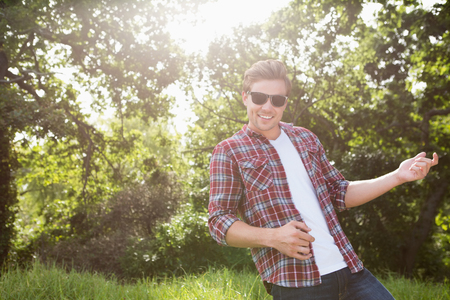air guitar: Handsome hipster playing air guitar on a sunny day