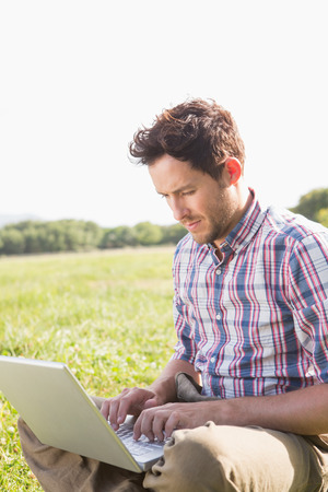 country living: Young man using laptop in the countryside on a sunny day Stock Photo