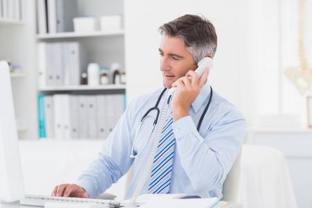 hablando por celular: Doctor de sexo masculino que usa el teléfono mientras se trabaja en el ordenador en la mesa en la clínica