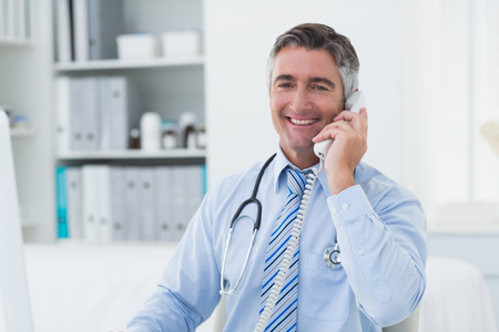 healthcare professional: Portrait of confident male doctor using telephone in clinic