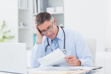 tensed: Tensed male doctor reading document at table in clinic