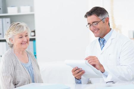 recetas medicas: Recetas escritura del doctor de sexo masculino feliz para el paciente mayor en la cl�nica