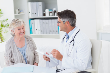 doctor and patient: Happy doctor writing prescriptions for senior female patient in clinic Stock Photo
