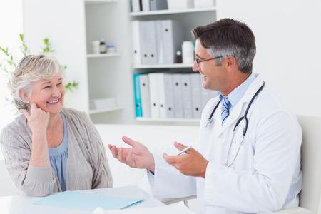 lekarz: Szczęśliwy mężczyzna lekarz omawia z wyższych pacjenta na stole w klinice Zdjęcie Seryjne