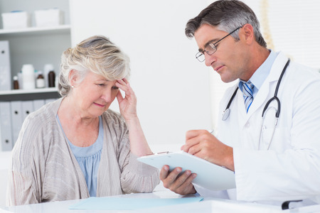 Doctor explaining prescription to senior female patient in clinic photo