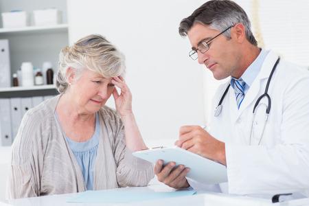 mujeres maduras: M�dico explicando la prescripci�n a los pacientes de sexo femenino mayor en la cl�nica