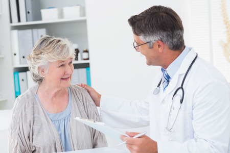 consoling: Male doctor consoling senior woman in clinic Stock Photo