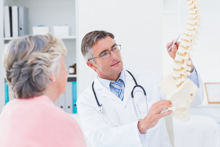 human spine: Male doctor explaning anatomical spine to senior woman in clinic