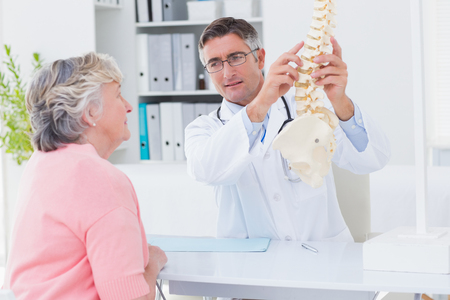 Male doctor explaning anatomical spine to female patient in clinic