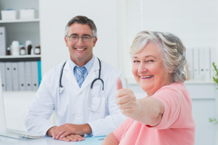 looking up: Portrait of happy female patient showing thumbs up sign while sitting with doctor in clinic