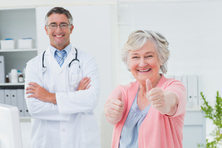 happy patient: Portrait of happy female patient showing thumbs up sign while standing with doctor in clinic