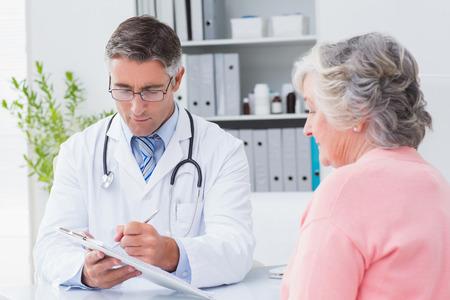 男性医師のクリニックで年配の女性に処方を説明します。