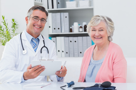 Portrait of happy male doctor holding clipboard while sitting with senior patient in clinic