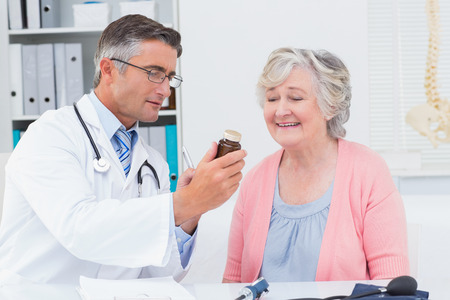 Male doctor showing medicine bottle to female patient in clinic photo