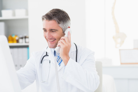 phone call: Happy male doctor using landline phone in clinic