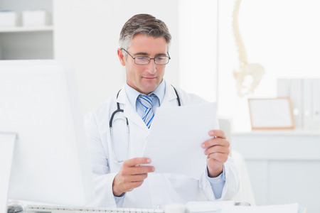 Male doctor reading document in clinic photo