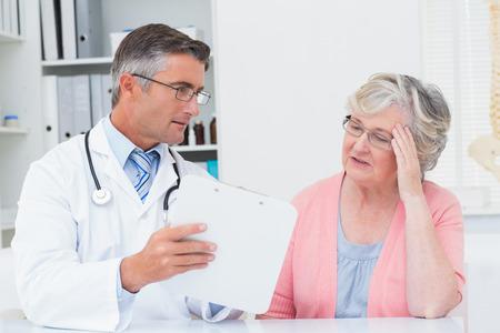 tensed: Male doctor explaining prescriptions to tensed senior woman in clinic