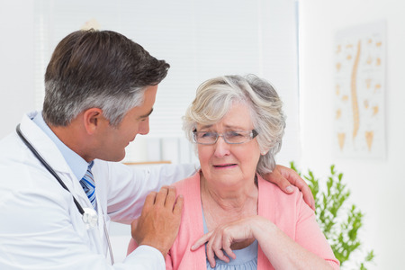consoling: Male doctor consoling senior female patient in clinic Stock Photo