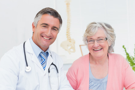 male doctor: Portrait of happy doctor and female patient in clinic