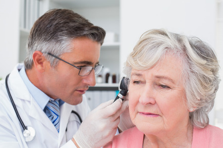 Male doctor examining female patients ear with otoscope in clinic