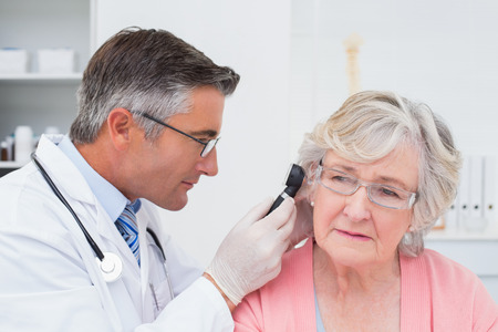 examining: Doctor examining female patients ear with otoscope in clinic