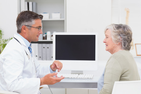 computer monitor: Side view of male doctor conversing with senior patient at table in clinic Stock Photo
