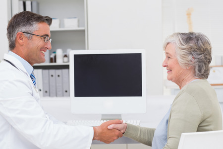 Side view of male doctor and female patient shaking hands in clinic photo