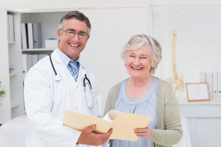 Portrait of happy male doctor and female patient with reports in clinic