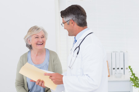 an elderly person: Male doctor and female patient conversing over reports in clinic