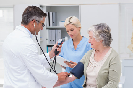 noting: Doctor checking senior patients blood pressure while nurse noting it in clinic