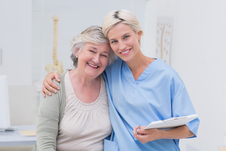 Hospital care: Portrait of friendly nurse with arm around senior patient standing in clinic