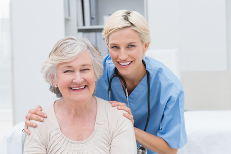 Portrait of friendly nurse with hands on senior patients shoulders in clinic