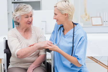 hand job: Smiling female nurse checking flexibility of patients wrist in clinic Stock Photo